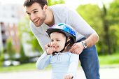 foto of father daughter  - Father helping daughter with bike helmet - JPG