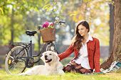 Beautiful female sitting on a grass with her labrador retriever dog in a park