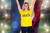 Excited football fan in brasil tshirt holding netherlands flag against large football stadium with brasilian fans