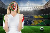 Excited iran fan in face paint cheering against large football stadium with brasilian fans