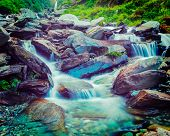Vintage retro effect filtered hipster style travel image of cascade of Bhagsu waterfall in Himalayas