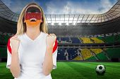 Excited german fan in face paint cheering against large football stadium with brasilian fans