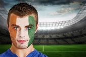 Composite image of ivory coast football fan in face paint against large football stadium with lights