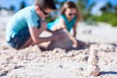 Sandman build from exotic pink sand with two kids building sandcastle on background while on beach h