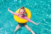 Adorable little girl with yellow inflatable ring swimming in a pool on summer vacation