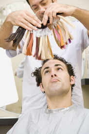 stock photo of hair dye  - A man is sitting in a salon and is contemplating hair colors - JPG