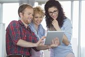 Businesswomen with male colleague using tablet PC in creative office