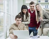 Young business people looking at laptop in meeting
