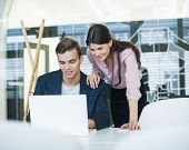 Young businessman and businesswoman using laptop at table in office