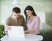 Young businessman and businesswoman using laptop at office table