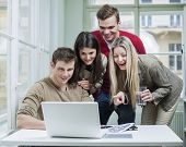 Happy business people using laptop in meeting