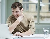 Young businessman using laptop at desk in office