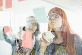 Businesswomen reading sticky notes on glass wall in creative office