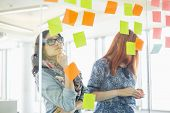 Creative businesswomen reading sticky notes on glass wall in office