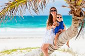 Mother and daughter sitting on palm at perfect Caribbean beach