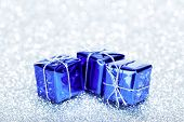 Small boxes with decorative holiday gifts on silver bokeh background