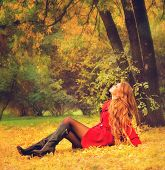 Young woman dressed in red coat relaxing in autumn park.