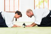 Man and woman take a bow to greet at Aikido martial arts school