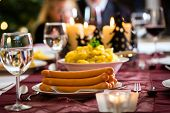 stock photo of wieners  - Family celebrating Christmas eve with traditional dinner Wiener sausages and potato salad - JPG
