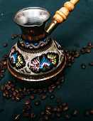 Decorative vintage Arabic Cezve for making Turkish coffee surrounded by whole roasted coffee beans below