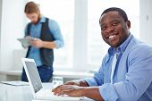 Modern African-american businessman looking at camera while networking on background of male co-worker