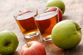 Glass of apple juice with apples on the table