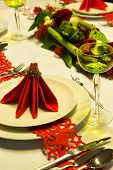 Christmas table decorated with red napkins and flower arrangement