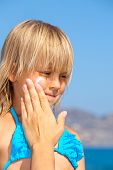 Mother apply sunblock cream on daughter's cheek