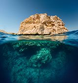 Split shot with coral reef underwater and rocky land of the Ras Muhammad National Park, Red Sea, Egypt