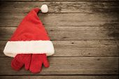 Santa's Hat And Red Mitten On Old Wooden Background