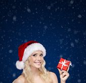 Woman in Christmas cap hands present wrapped with red paper, on blue background
