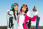 Half-length portrait of two female downhill skier friends thumbing up