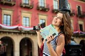 Female Tourist Sightseeing And Holding Guide Map