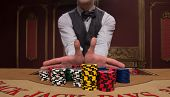 pic of shiting  - Handsome  dealer giving  red blue and shite chips in piles  on  table with  in casino looking at camera - JPG