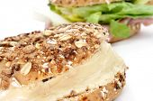 closeup of a brown bagel topped with different seeds, such as sesame and poppy seeds, filled with cheese spread