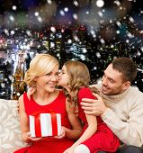 christmas, holidays, family and people concept - happy mother, father and little girl with gift box kissing over snowy night city background