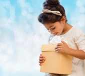 holidays, presents, christmas, childhood and people concept - smiling little girl with gift box over blue lights background