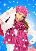 happiness, winter holidays, christmas and people concept - smiling young woman in hat and scarf with shopping bags over blue snowy background