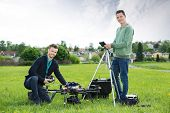 Portrait of happy technicians working on UAV helicopter in park