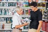 Father and son looking at packed cordless drill in hardware store