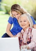 stock photo of granddaughter  - Smiling senior woman and granddaughter using laptop at nursing home porch - JPG
