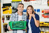 Woman showing something to man holding basket of tools in hardware store