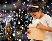 holidays, presents, christmas, childhood and people concept - smiling little girl with gift box over snowy night city background