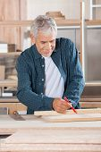 Happy senior male carpenter marking on wood with pencil in workshop
