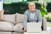 Portrait of smiling senior man with laptop sitting on couch at nursing home porch