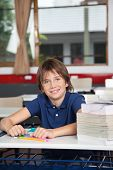 Portrait of cute schoolboy with stack of books and globe at desk in classroom