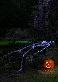 Skeleton with lit pumpkin in the ruins of an ancient abbey