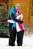 Full-length portrait of embracing couple who wears warm caps and jackets during winter holidays