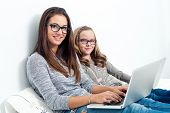 Teen Girl With Younger Sister On Bed With Laptops.