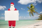 christmas, holidays, advertisement, travel and people concept - man in costume of santa claus with white blank billboard over tropical beach background